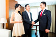 Asian hotel manager greeting guests in roorm