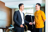 Asian hotel bell boy servicing guest in room