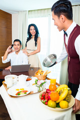 Asian room service waiter serving food in room