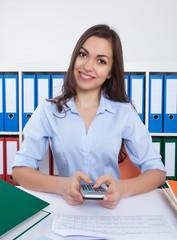 Frau mit langen braunen Haaren und Taschenrechnerim Büro