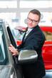 Verkäufer verkauft Auto im Autohaus