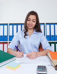 Frau mit langen braunen Haaren im Büro macht Notizen