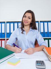 Sympathische Frau mit langen braunen Haaren im Büro