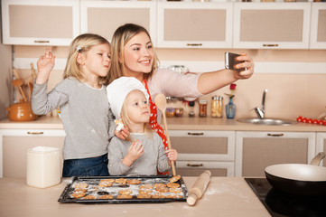 Cute girls and their mother making photo while cooking