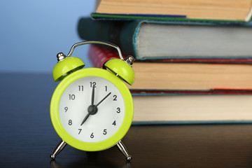 Stack of books with alarm clock