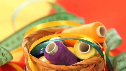 Top of basket with colorful threads, measuring tape, confidant
