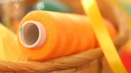 Yellow bobbin of thread with ribbon in the basket, close up