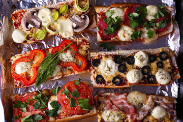 Different sandwiches with vegetables and cheese on pan close up