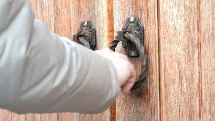 Hand knocking on old-fashioned ancient wooden gate or door