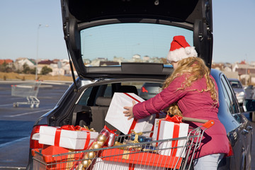Girl with Christmas gifts near a car