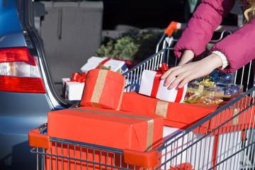 Shopping cart with carton, near a car