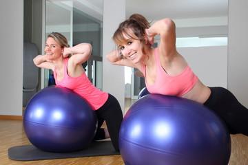Zwei Frauen beim Fittness auf Bällen mit Händen im Nacken