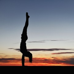 silhouetted gymnast doing handstand in sunset