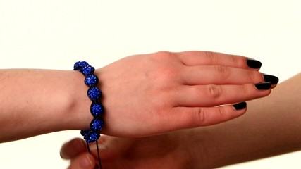 Woman shows popular bracelet shamballa on hand, white background