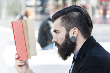 young hipster reading a book sitting outdoors