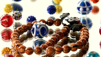 Colorful beads on white background, cam moves to the left