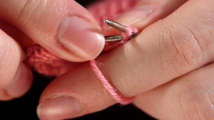 Woman sits and knits pink scarf, fine knit, close up, slow