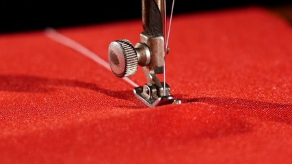 Old sewing machine on red cloth, close up, slow motion