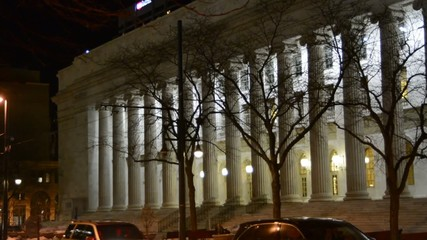 Panning from street level across columns of a courthouse