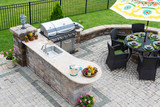 Outdoor kitchen and dining table on a paved patio