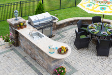 "Постер, картина, фотообои ""Outdoor kitchen and dining table on a paved patio"""