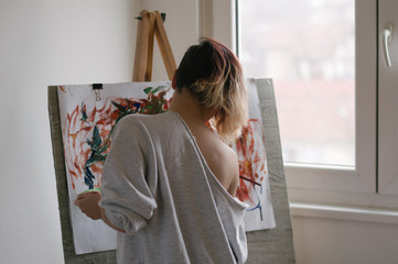 Portrait of a girl while painting on the easel