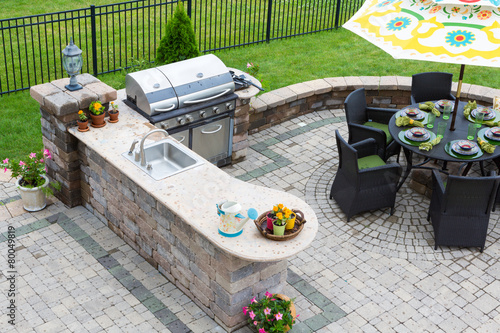 Outdoor kitchen and dining table on a paved patio - 80049819