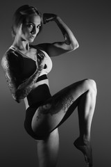 Black and white image of a young female fitness model posing.