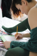 A girl sitting on the bed and draws on white paper