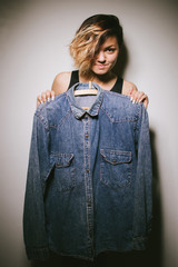 A girl holds a denim shirt on a hanger in front of her body