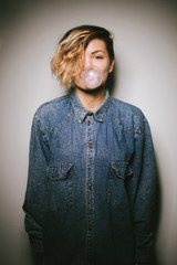 Girl in denim shirts, blowing bubbles with chewing gum