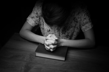 Woman hands praying with a bible, vintage tone