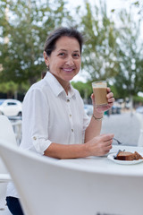 mature woman sitting at  table in  cafe