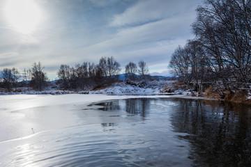 Small winter lake.  Cloudy. Lowering sky