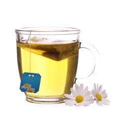 Cup of chamomile tea with chamomile flowers and tea bag isolated