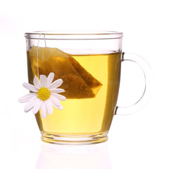 Cup of chamomile tea with chamomile flower and tea bag isolated