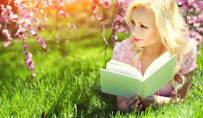 Girl with Book. Blonde Young Woman Lying on the Grass