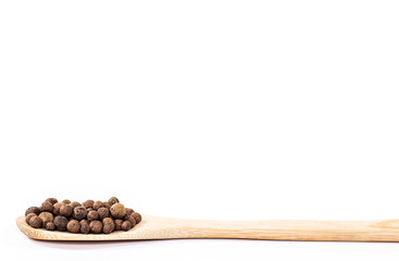 isolated black pepper on wooden spoon