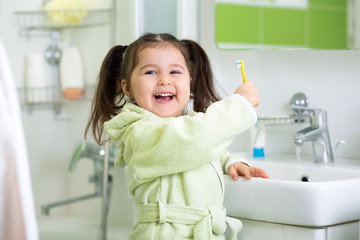 Child brushing teeth in bathroom