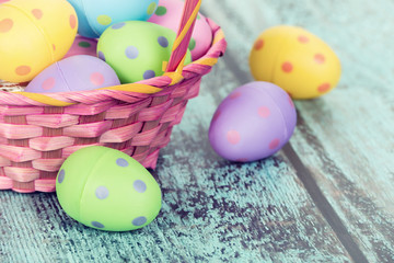 Pink Easter basket with eggs on vintage wooden background
