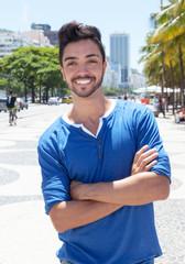 Modischer junger Mann steht an der Avenida Atlantica in Rio