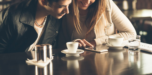 Friends at the cafe using a mobile phone
