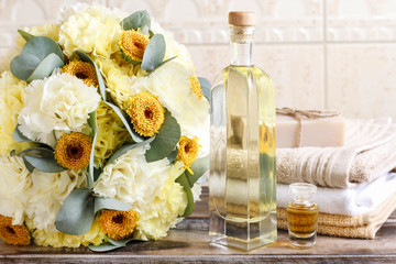 Bottle of essential oil, bouquet of yellow carnation flowers