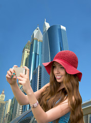 Girl in a red hat is taking a selfie in front of skyscrapers in
