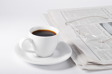 A cup of coffee, glasses and newspaper.