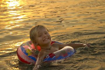 little girl swimming on rubber ring