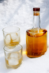 Bottle of brandy with two glasses in the snow