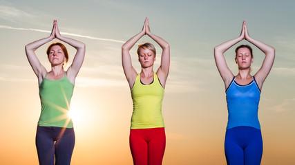 Three girls practicing yoga in sunset