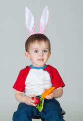 Boy dressed as Easter bunny with egg and carrot