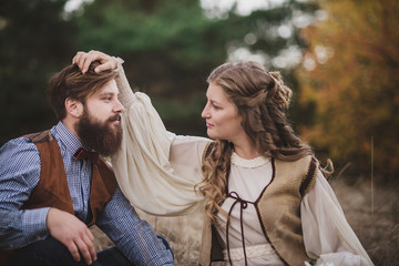 Bearded man and nice woman in the wood